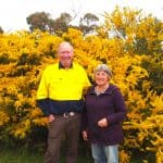 Graeme and Dianne Johnson in front of a beautiful wattle tree on their property